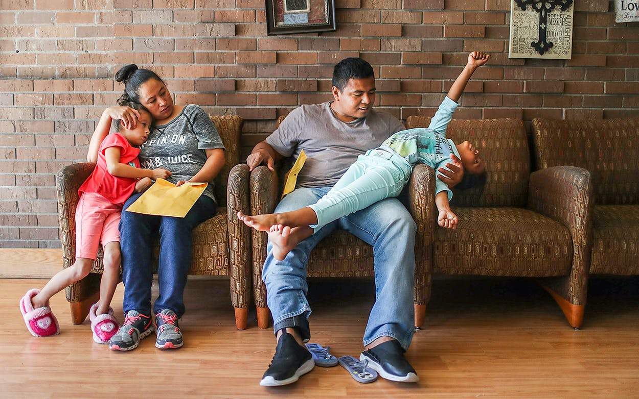 A woman, identified only as Heydi and her daughter Mishel, 6, and a man, identified only as Luis, and his daughter, Selena, 6, relax together in an Annunciation House facility after they were reunited with their children on July 26, 2018 in El Paso.