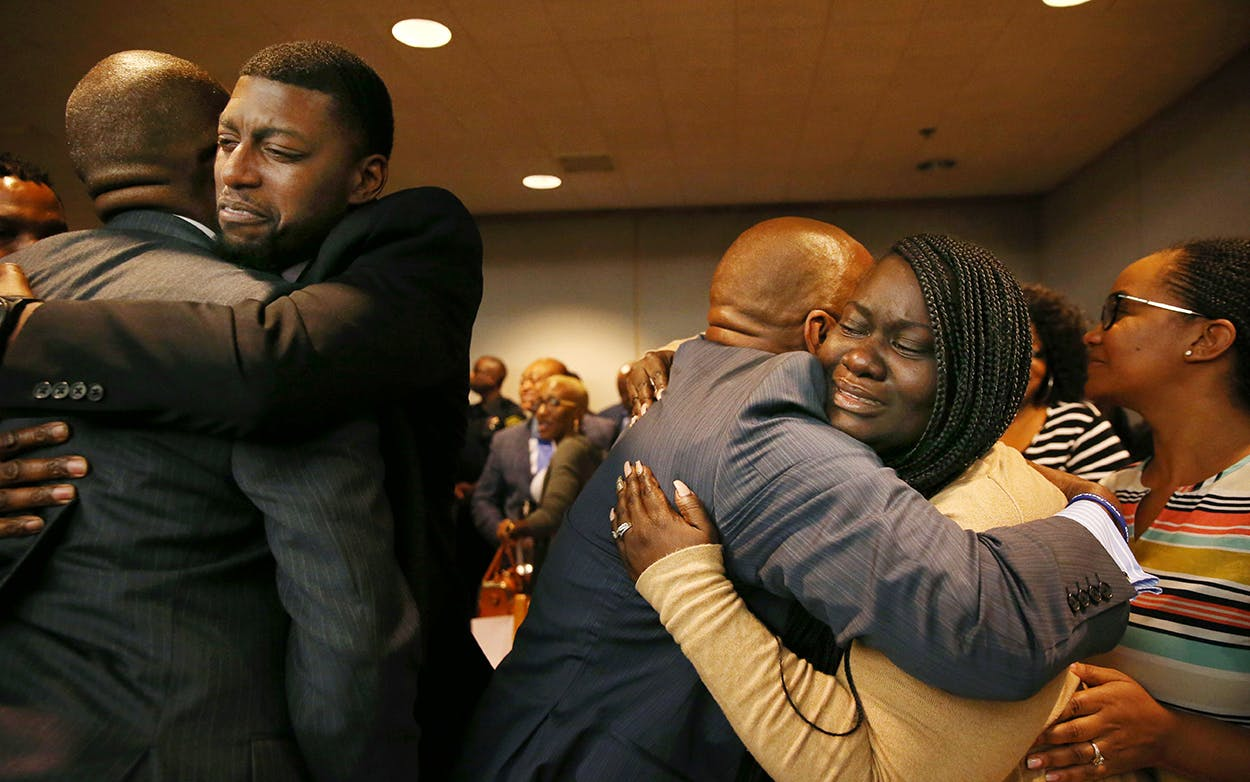 Parents of Jordan Edwards, Odell and Charmaine Edwards (facing camera), hug prosecutor George Lewis (L) and family member Reggie Edwards (R), as they react to a guilty of murder verdict during the ninth day of the trial of fired Balch Springs police officer Roy Oliver, who was charged with the murder of 15-year-old Jordan Edwards, on August 28, 2018 in Dallas.