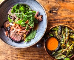 Sliced brisket and grilled snap peas at Loro