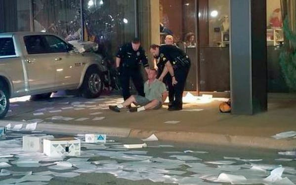 In this image taken from video by KDFW Fox 4 a man is detained after crashing his pickup truck into the side of the Fox affiliate television station building in downtown Dallas on Wednesday, Sept. 5, 2018.