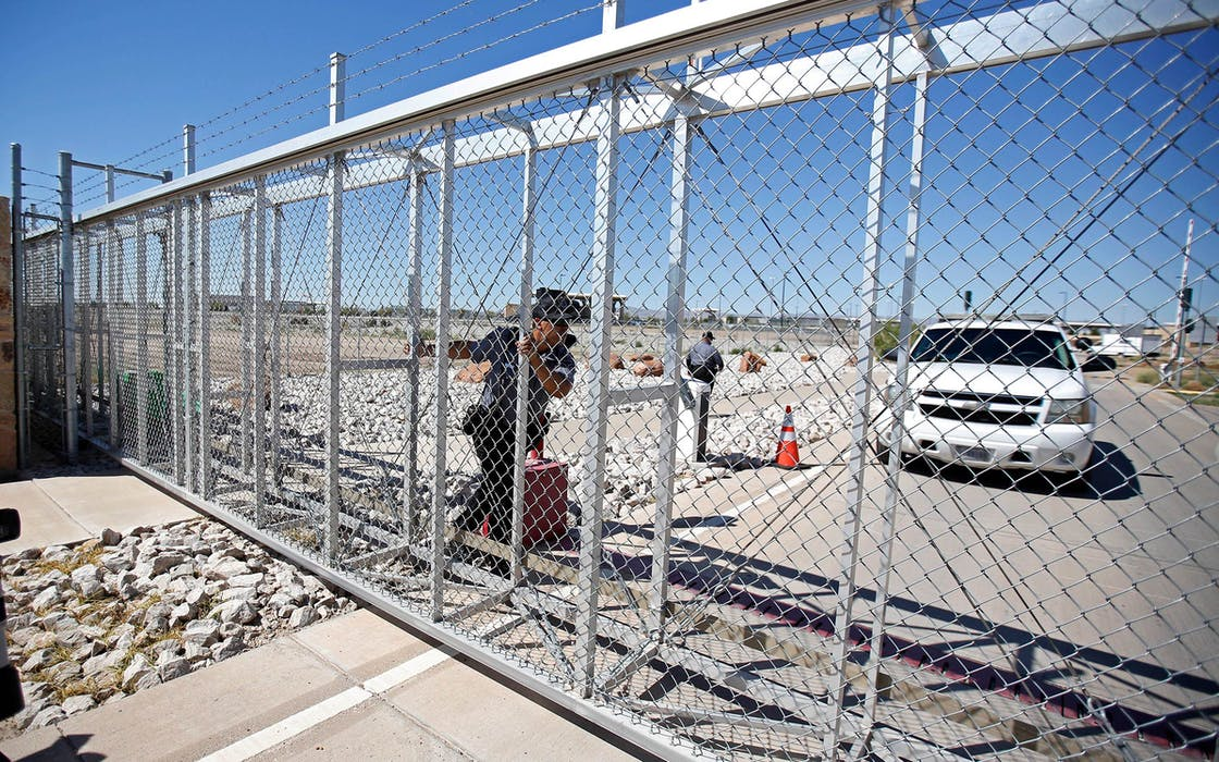 An agent with the Department of Homeland Security closes the exterior gate of the holding facility for immigrant children in Tornillo, Texas, near the Mexican border, Thursday, June 21, 2018.