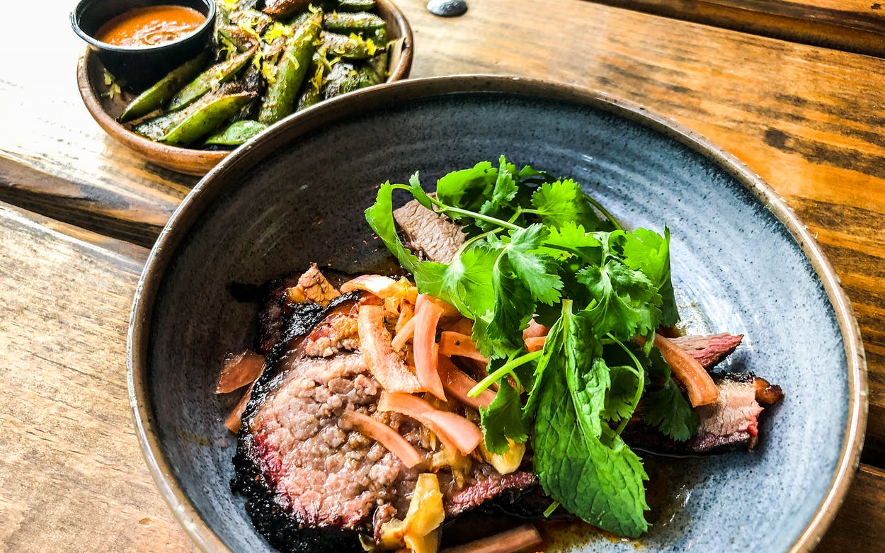 Sliced brisket and grilled snap peas at Loro in Austin.