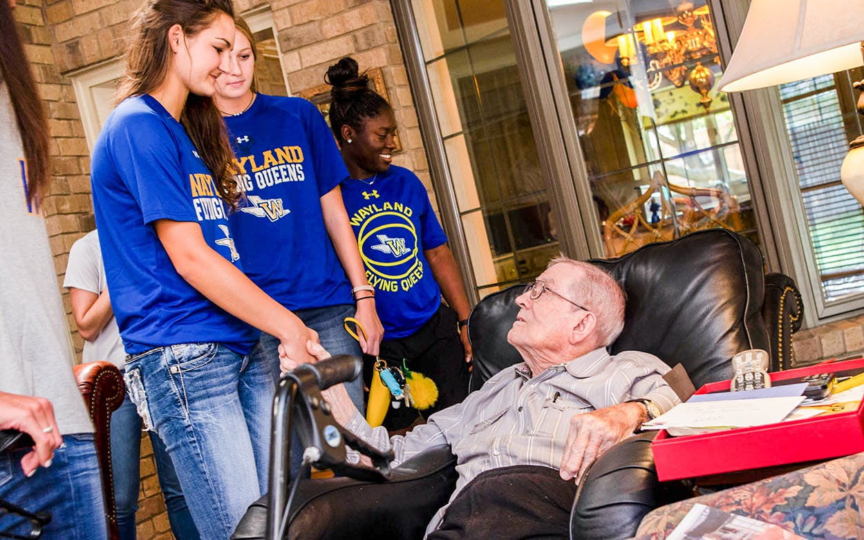 In honor of his 99th birthday, former coach Harley Redin shakes hands with current members of the Wayland Flying Queens basketball team on August 29, 2018.