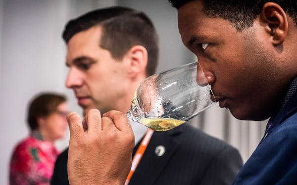 An attendee tastes a glass of wine at TEXSOM.
