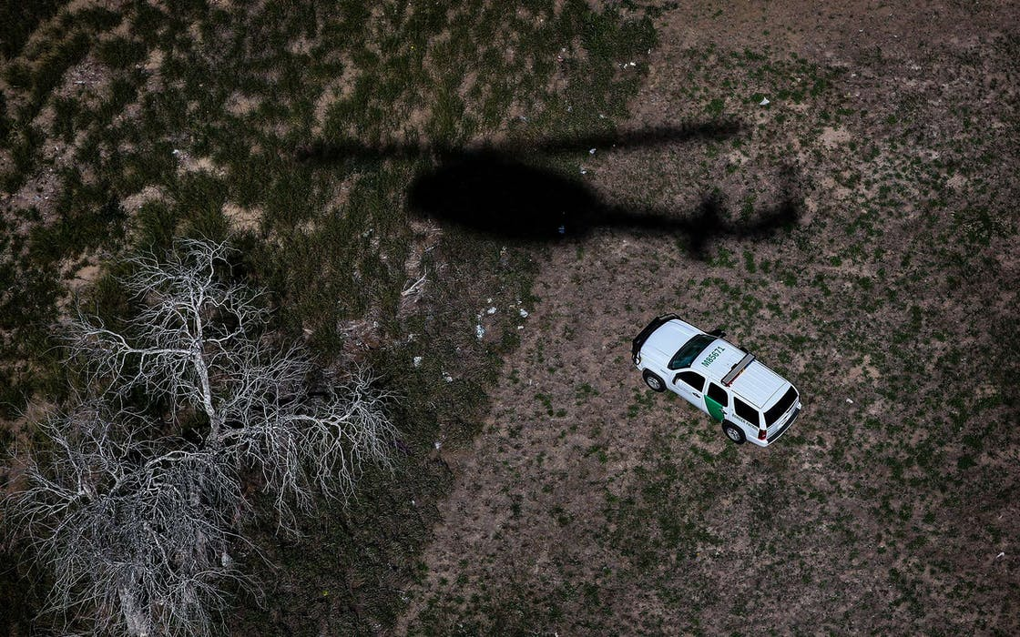 The shadow of a helicopter from U.S. Office of Air and Marine passes a U.S. Border Patrol vehicle as agents search for undocumented immigrants on September 11, 2014 in Falfurrias, Texas.