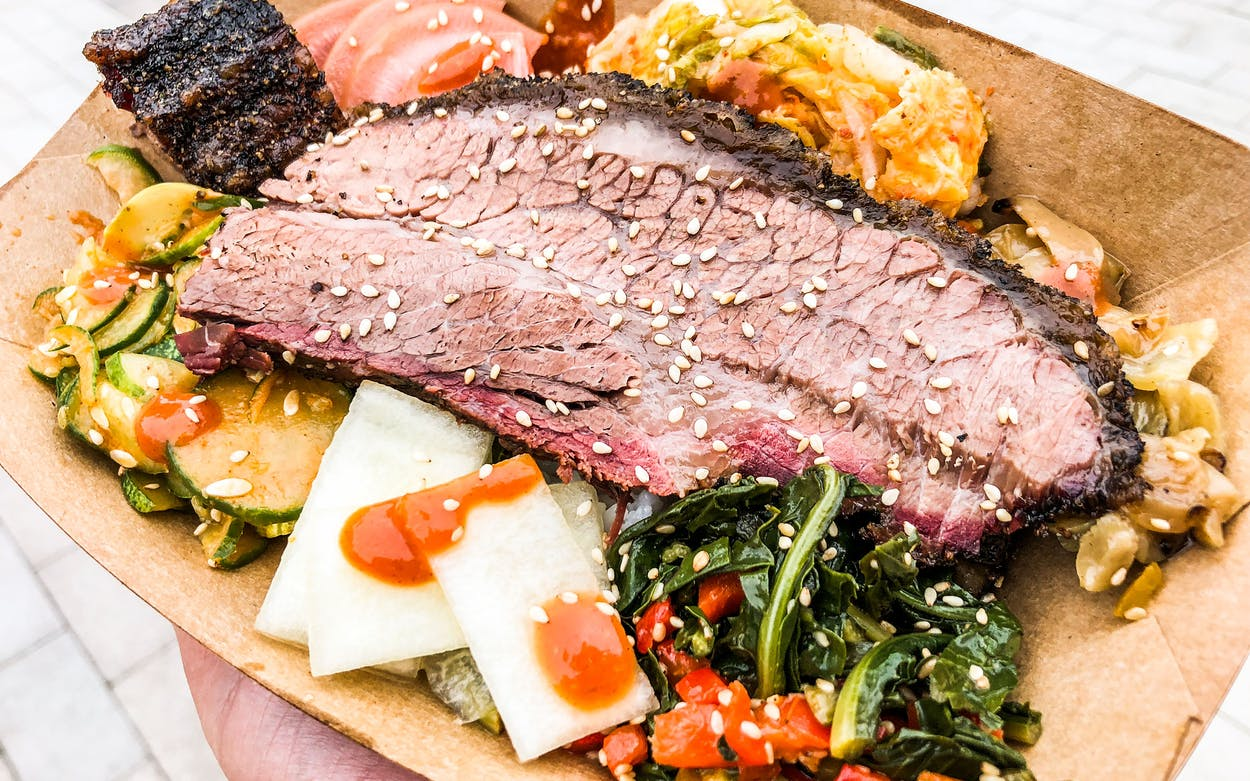 At LeRoy & Lewis BBQ, the bibimbap consists of a thick slice of smoked Ranger Cattle on top of rice, surrounded by banchan (fermented and pickled side dishes).