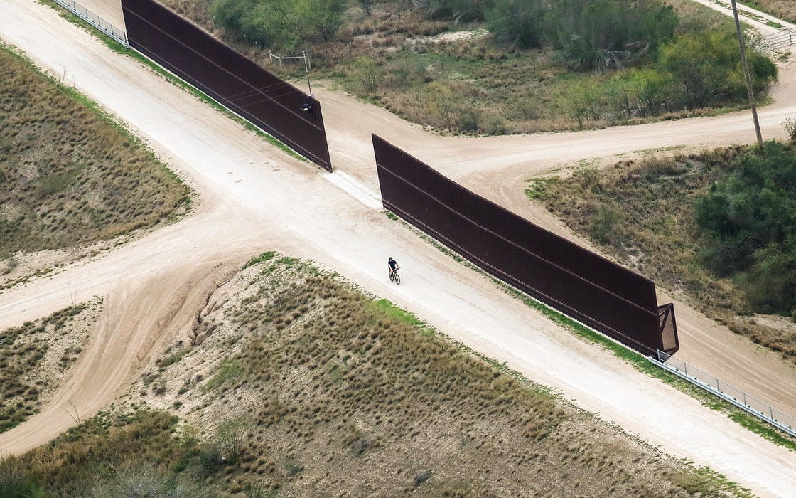A cyclist rides along a portion of the U.S.-Mexico border fence on February 21, 2018 in McAllen.