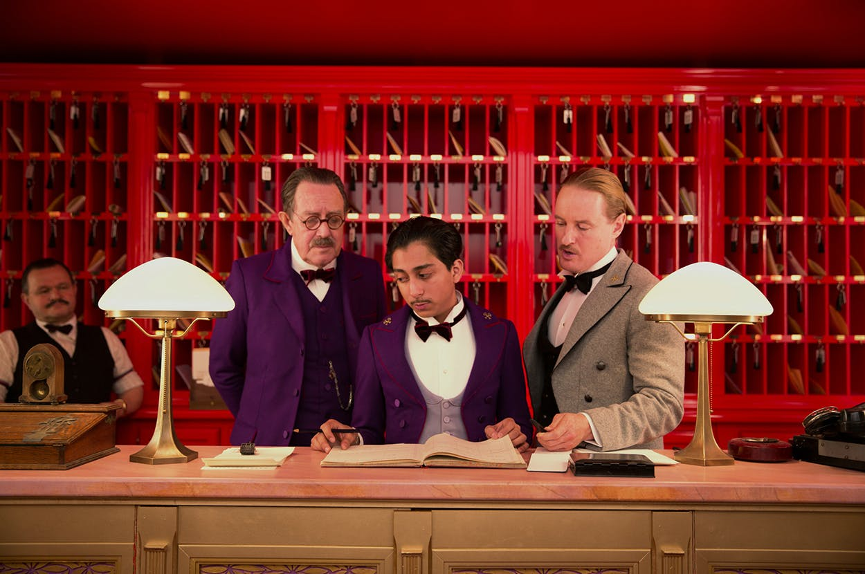 "Tony Revolori (center, as Zero) and Owen Wilson (right, as Chuck) in the 2014 film ""The Grand Budapest Hotel."""