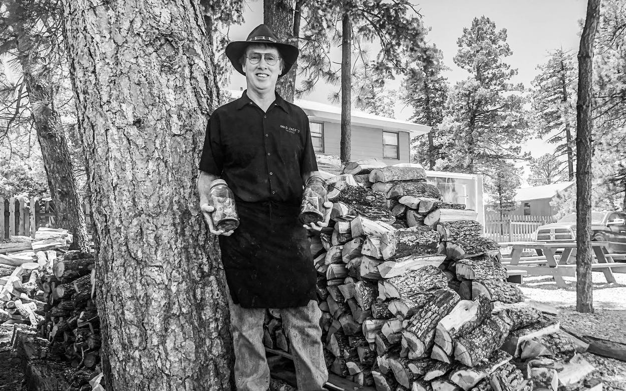 James Jackson stands next to a pile of Lockhart post oak wood.
