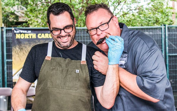 Aaron Franklin of Austin's Franklin Barbecue lets Southern Smoke co-founder and curator Chris Shepherd sample some of his brisket during the event that raised $425,000 for charity on September 30, 2018 in Houston.