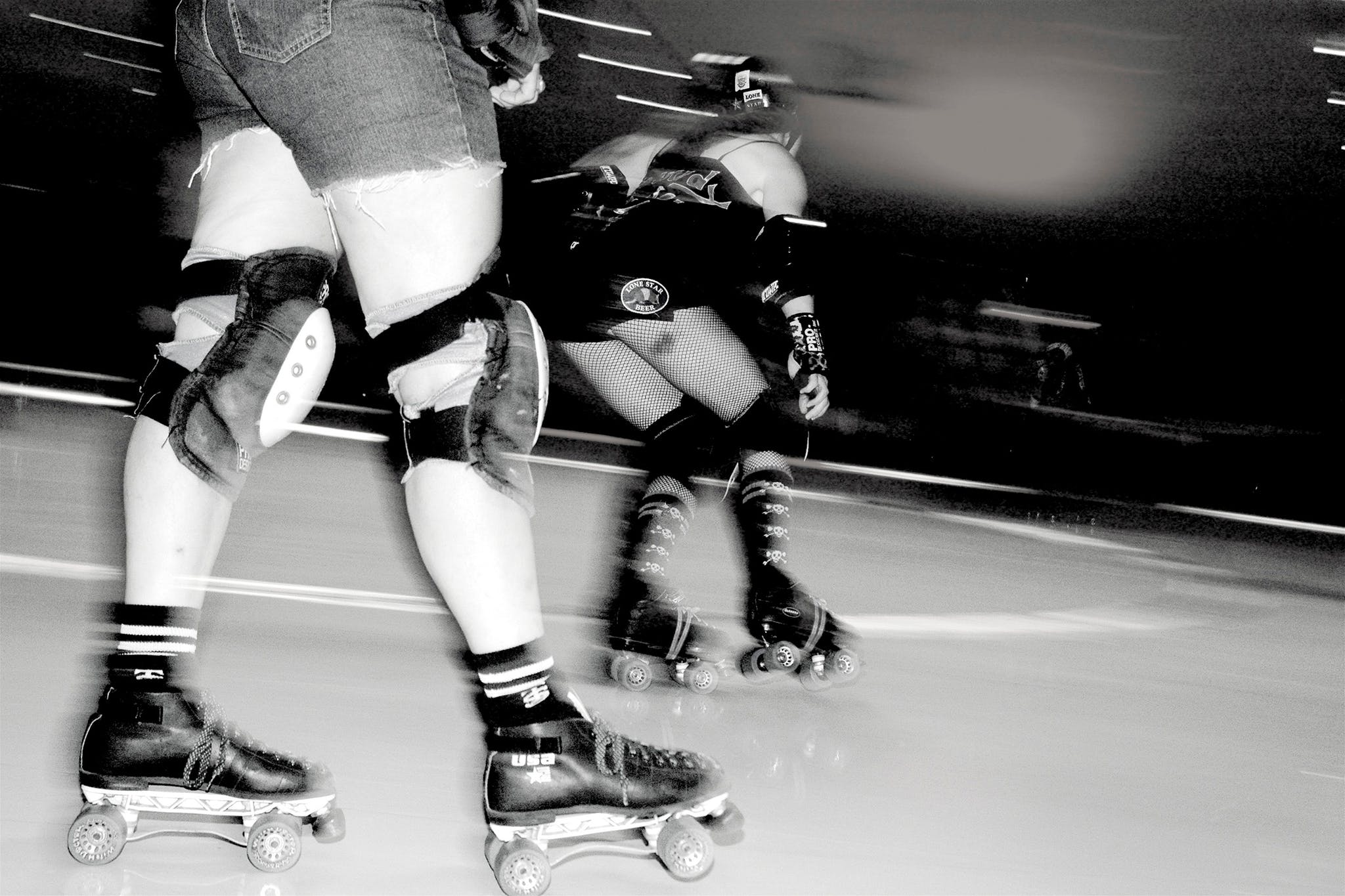Skaters with Texas Rollergirls round the rink in a roller derby bout.