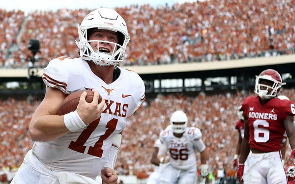 Sam Ehlinger #11 of the Texas Longhorns smiles as he runs into the endzone for a touchdown against the Oklahoma Sooners in the second quarter of the 2018 AT&T Red River Showdown at Cotton Bowl on October 6, 2018 in Dallas.