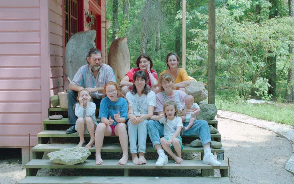 Top row (left to right): James Surls, Abbie Sporl, Charmaine Locke; second row (left to right): Lily Surls, Ruby Surls, ShawnTay Surls, Shannon Surls holding baby Molly Surls; Bottom row: Eva Surls. Taken on the steps of the Locke/Surls house, in Splendora in 1990.