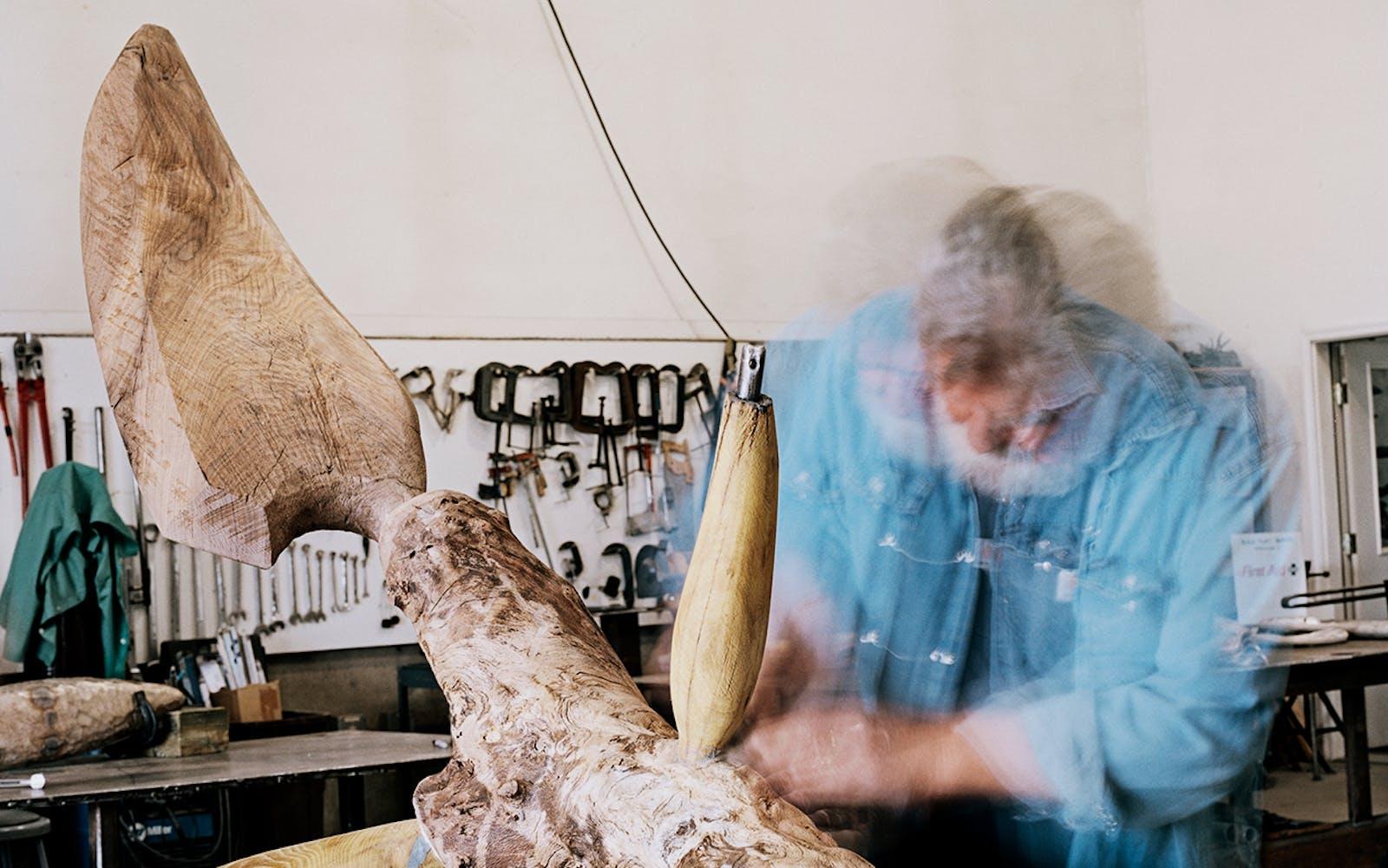 James Surls works on a wood sculpture titled