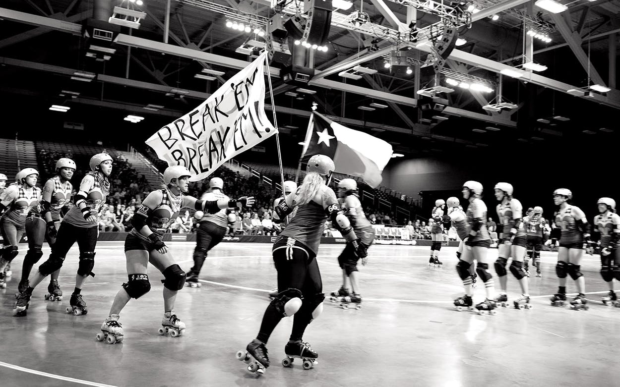 Roller derby team the Honky Tonk heartbreakers carry flags around the track