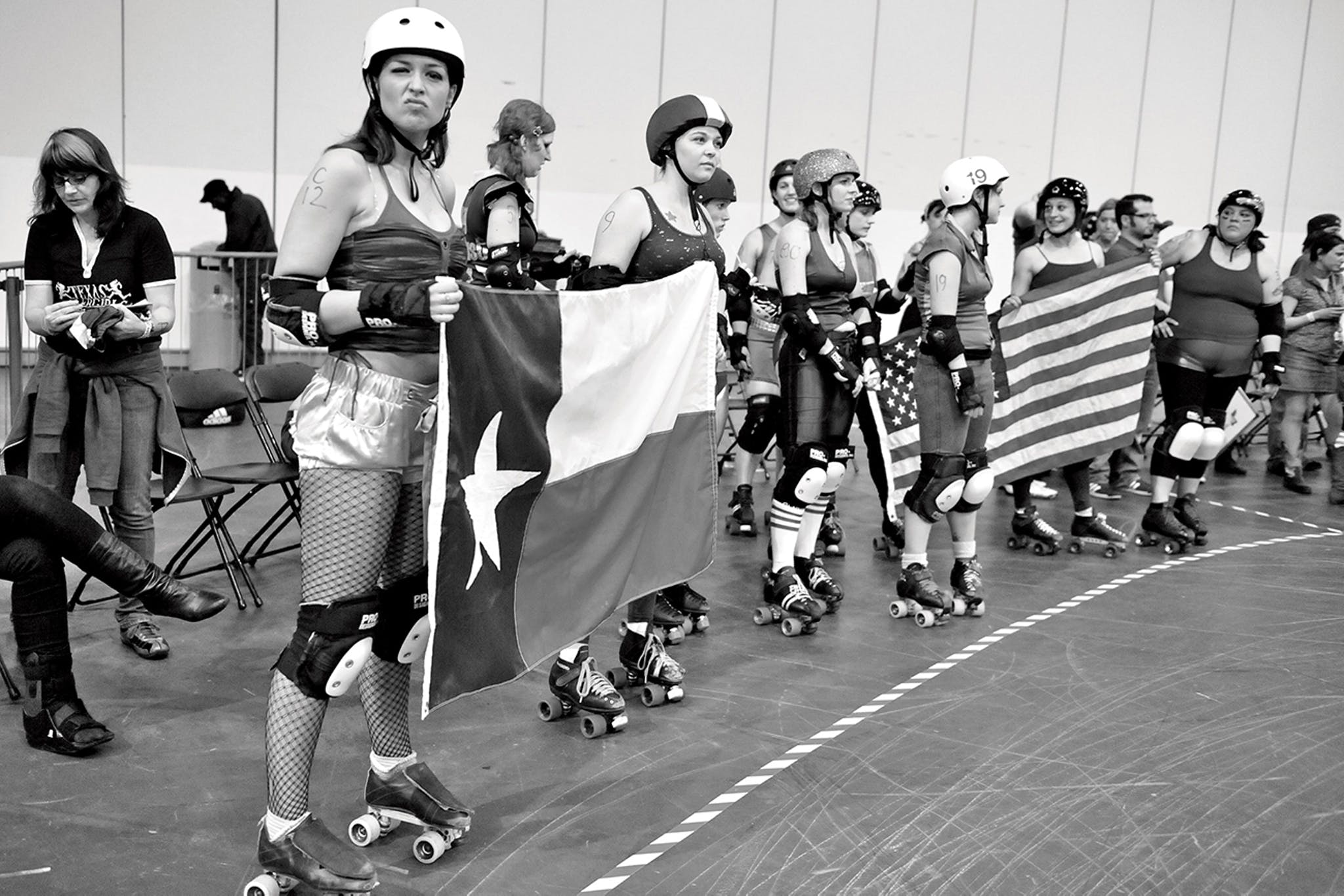 Members of the Texas Rollergirls hold Texas and American flags at a tournament in London