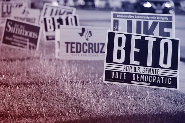 Campaign signs for Beto O'Rourke and Ted Cruz are crowded around the Carrollton Public Library on November 1, 2018 in Carrollton, Texas.
