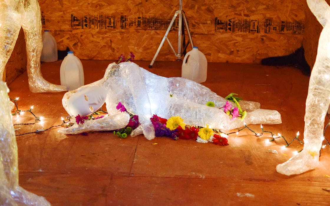 """Mannequins of children, created from transparent packing tape, are surrounded by flowers and strings of lights in RAICES' """"Abolish ICEbox"""" exhibit."""