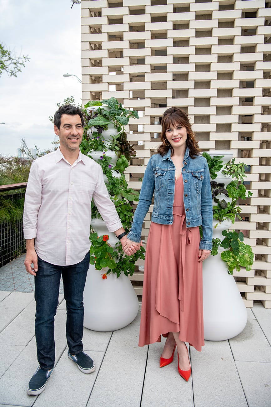 "Zooey Deschanel and her husband Jacob Pechenik in front of a couple of Lettuce Grow's ""Farms."""