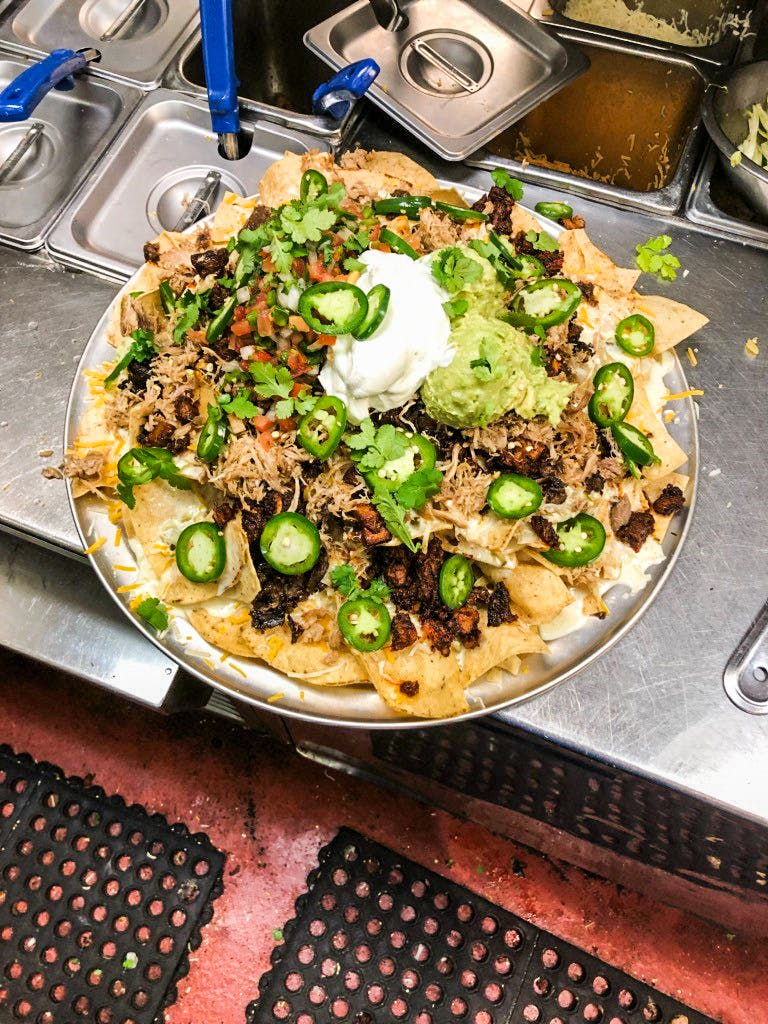 The Grande Nachos Supreme at Chispas in Austin are topped with barbacoa, duck confit and carne asada,