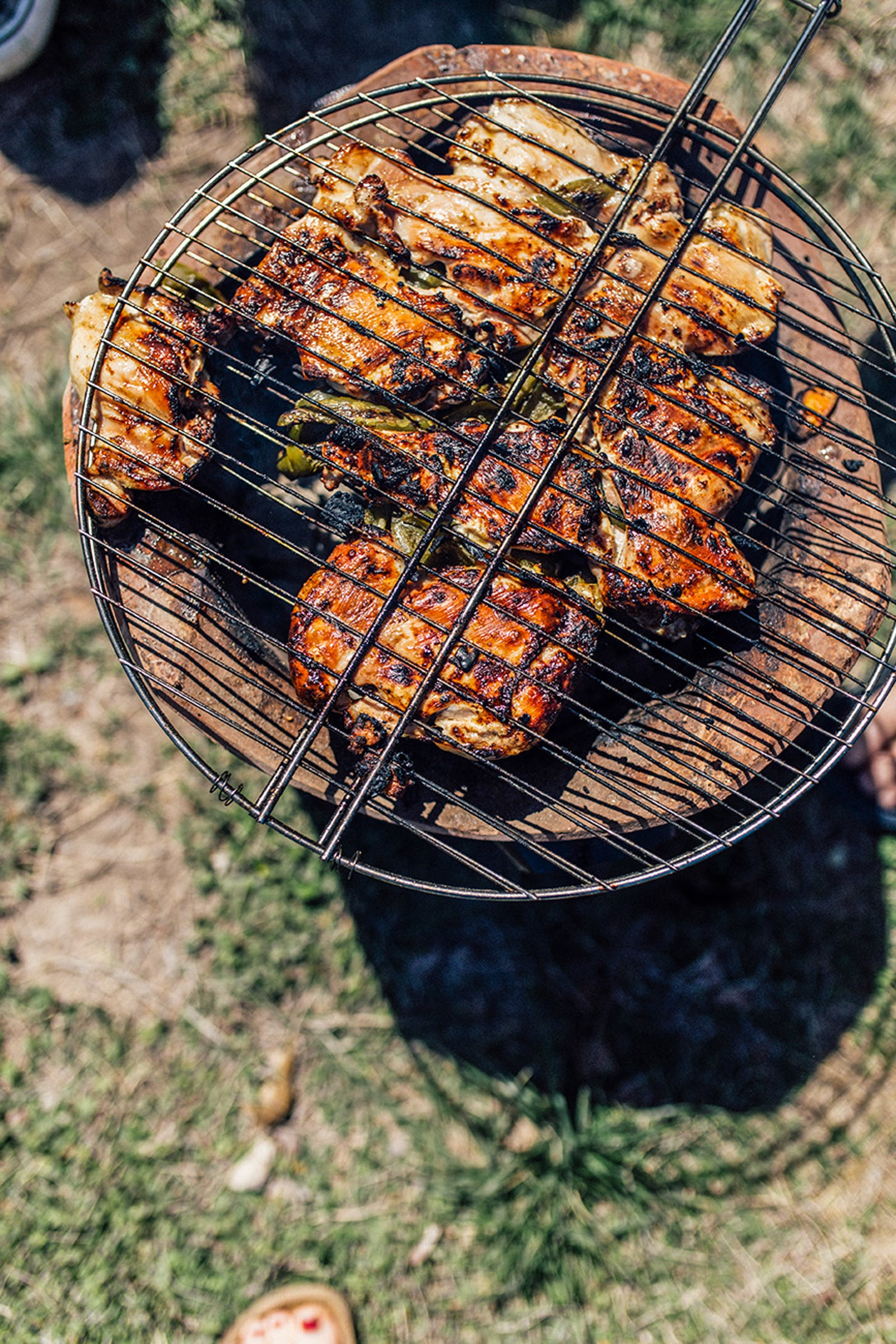 Chicken thighs charring on a small Burmese/Thai grill.