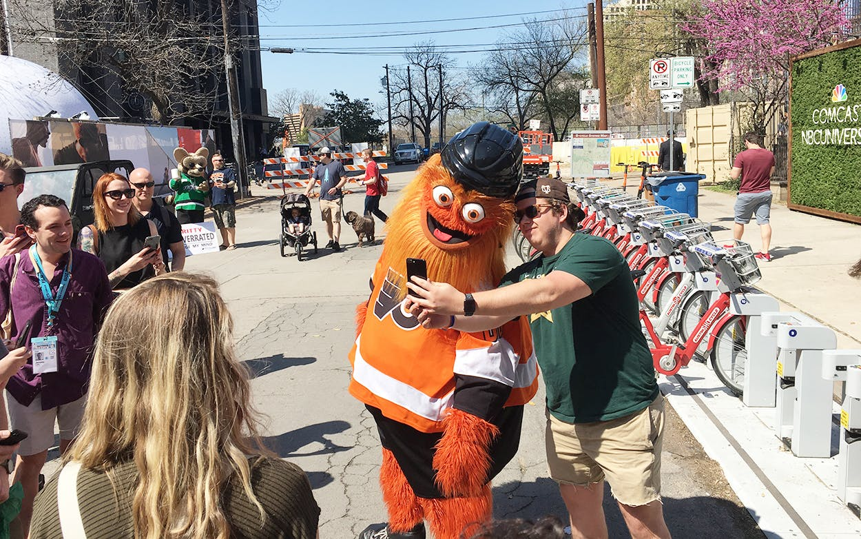 Philadelphia Flyers mascot Gritty posing for photos with fans outside on Rainey Street