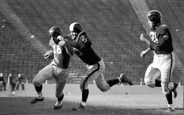 Dallas Texans players tackling Frank Gifford during the first game of the season, with empty seats in the background.