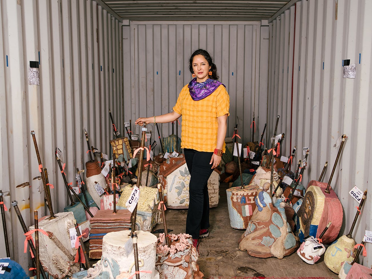 Cabrera in a storage unit containing sculptures that are to be hung.