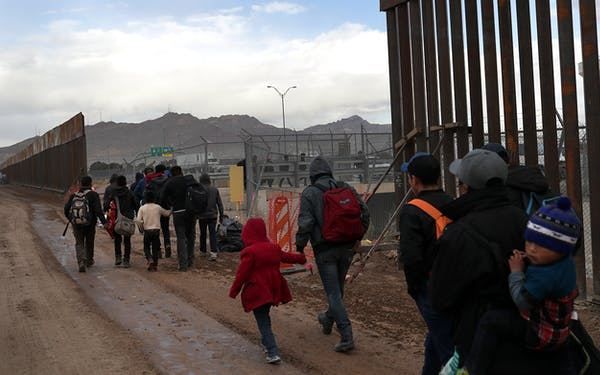 Central American immigrants walk between a gap in the border fence after crossing the Rio Grande from Mexico on February 01, 2019 in El Paso, Texas. The migrants turned themselves in to U.S. Border Patrol agents, seeking political asylum in the United States.