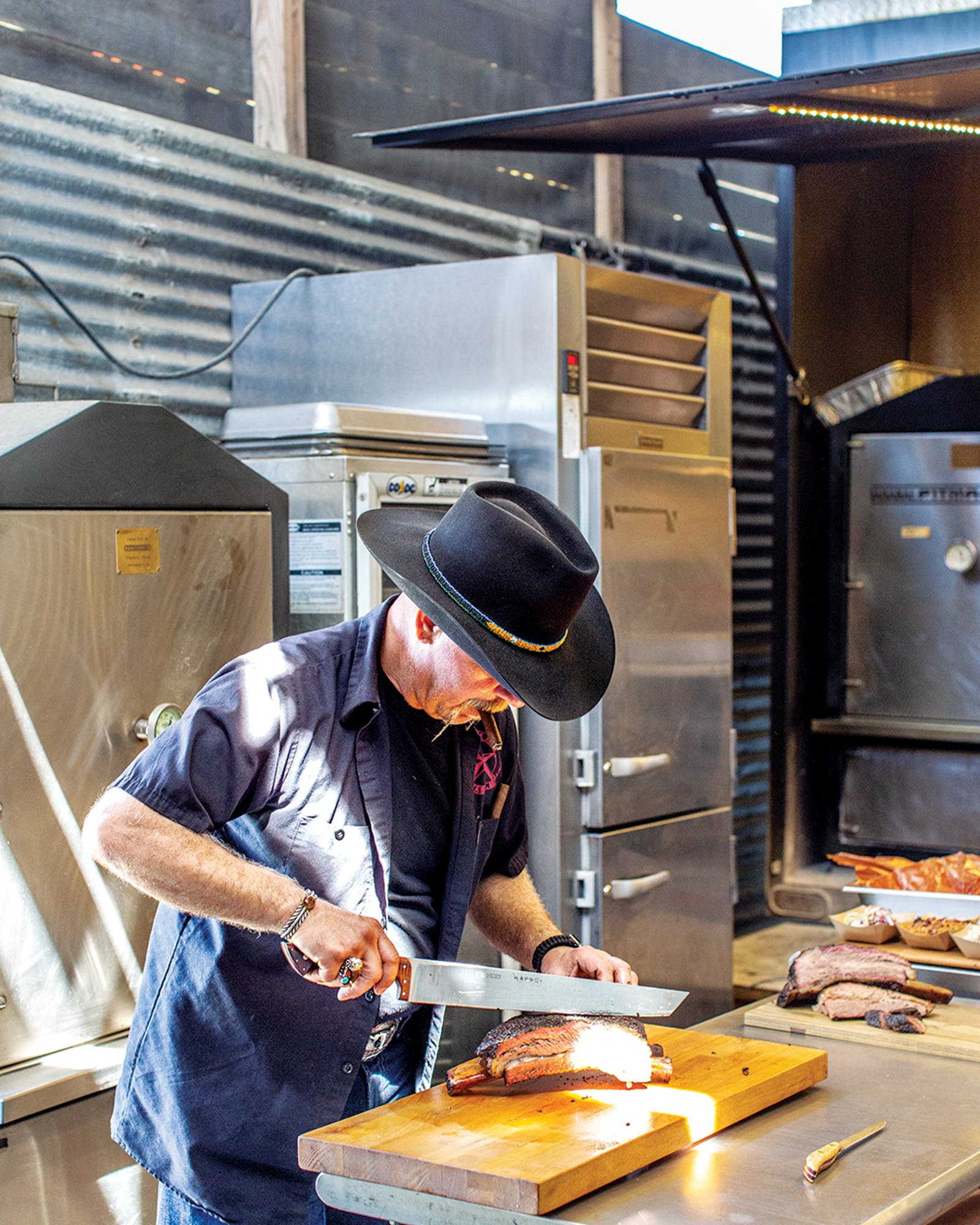 Harlem Road Texas BBQ's pitmaster Ara Malekian slicing beef ribs.
