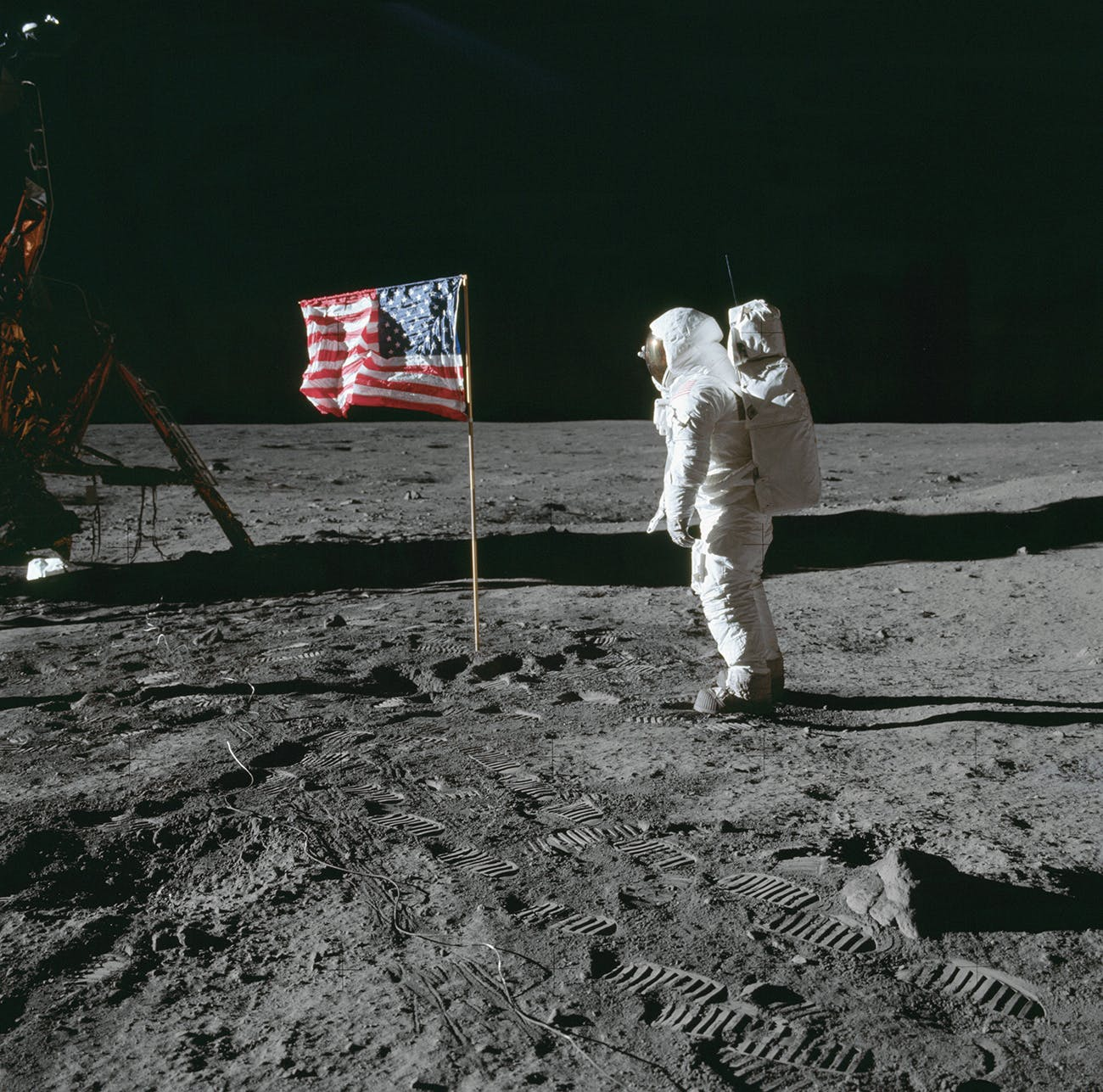 Astronaut Edwin E. Aldrin Jr., lunar module pilot of the first lunar landing mission, poses for a photograph beside the deployed U.S. flag during Apollo 11 extravehicular activity on the lunar surface on July 20, 1969.