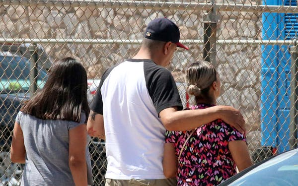 People walk out of an elementary school after family members were asked to reunite following a shooting at a shopping mall in El Paso on Saturday, Aug. 3, 2019.