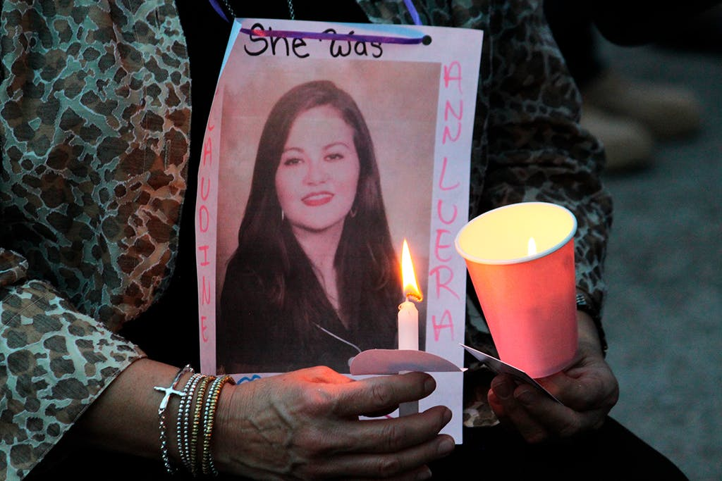 A family member holds a photo of Claudine Luera during a prayer vigil .