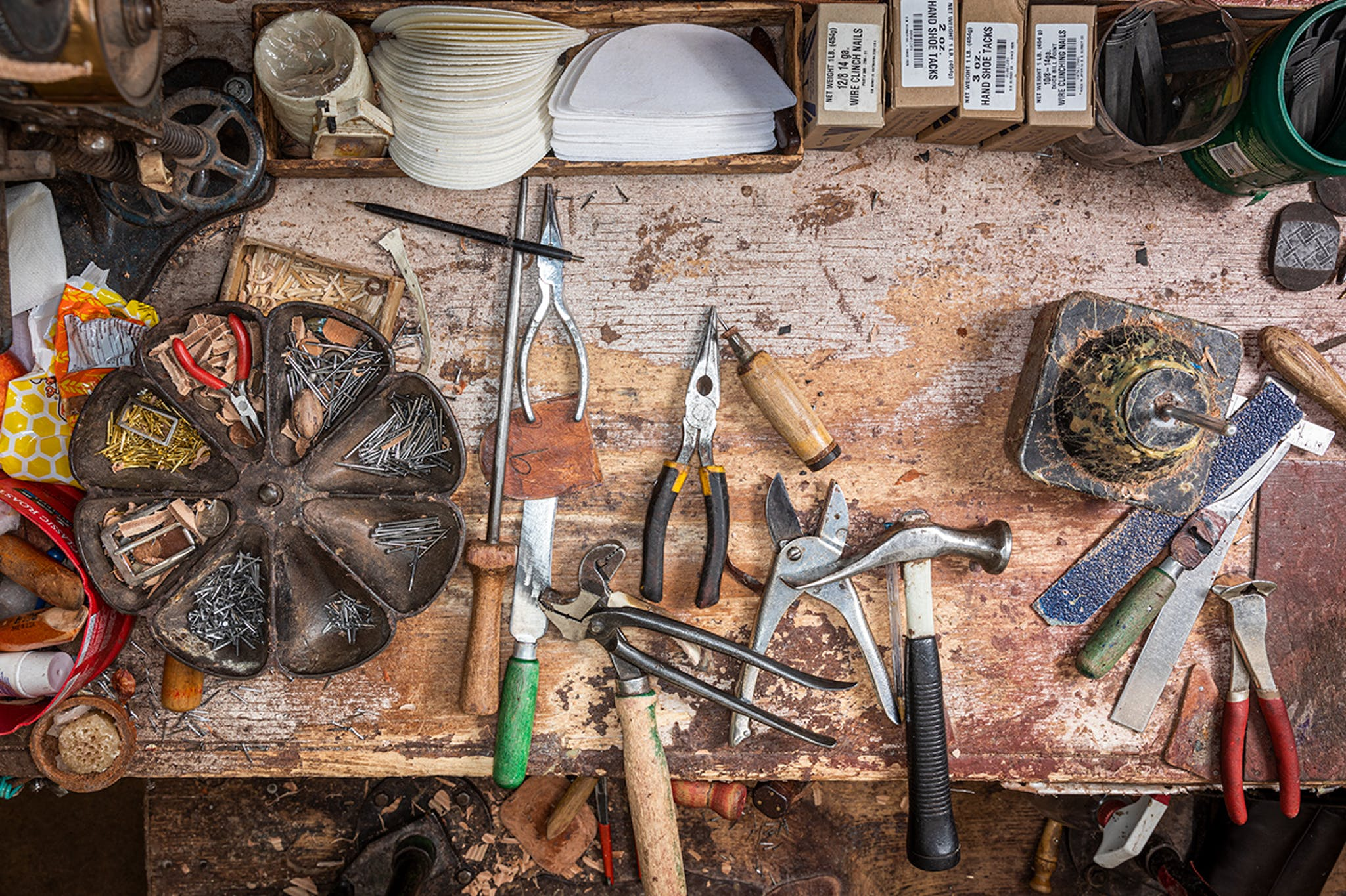 A well-worn work bench with sundry tools of the bootmaking trade.