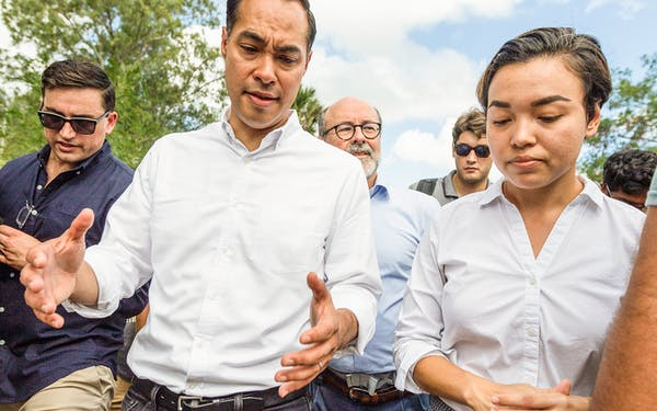 Democratic presidential candidate Julian Castro, left, asks Dani Marrero Hi about conditions for those seeking asylum Monday, Oct. 7, 2019, as they walk through a migrant campsite in Matamoros, Mexico.