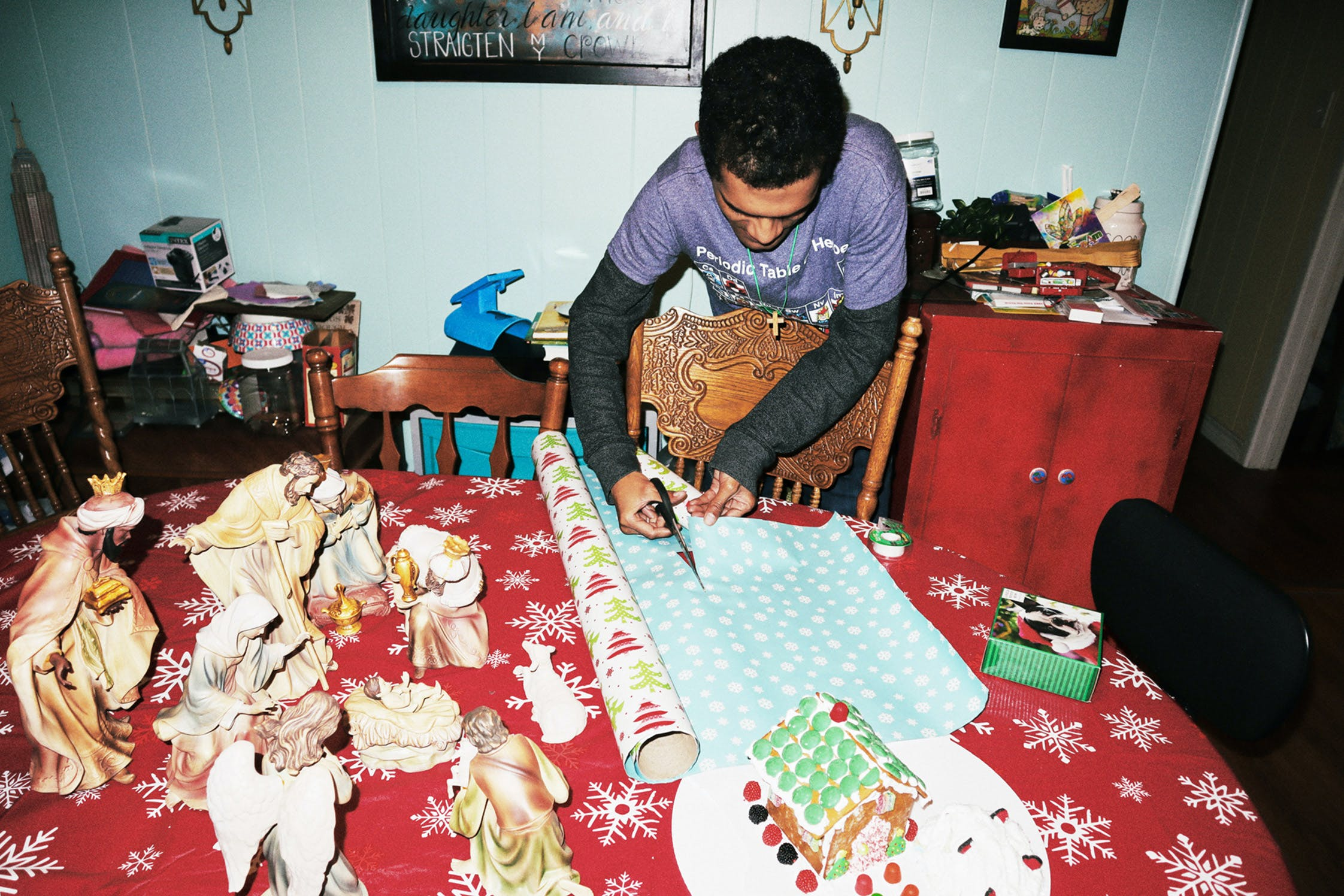 Chris cuts paper to wrap his Christmas gifts with.