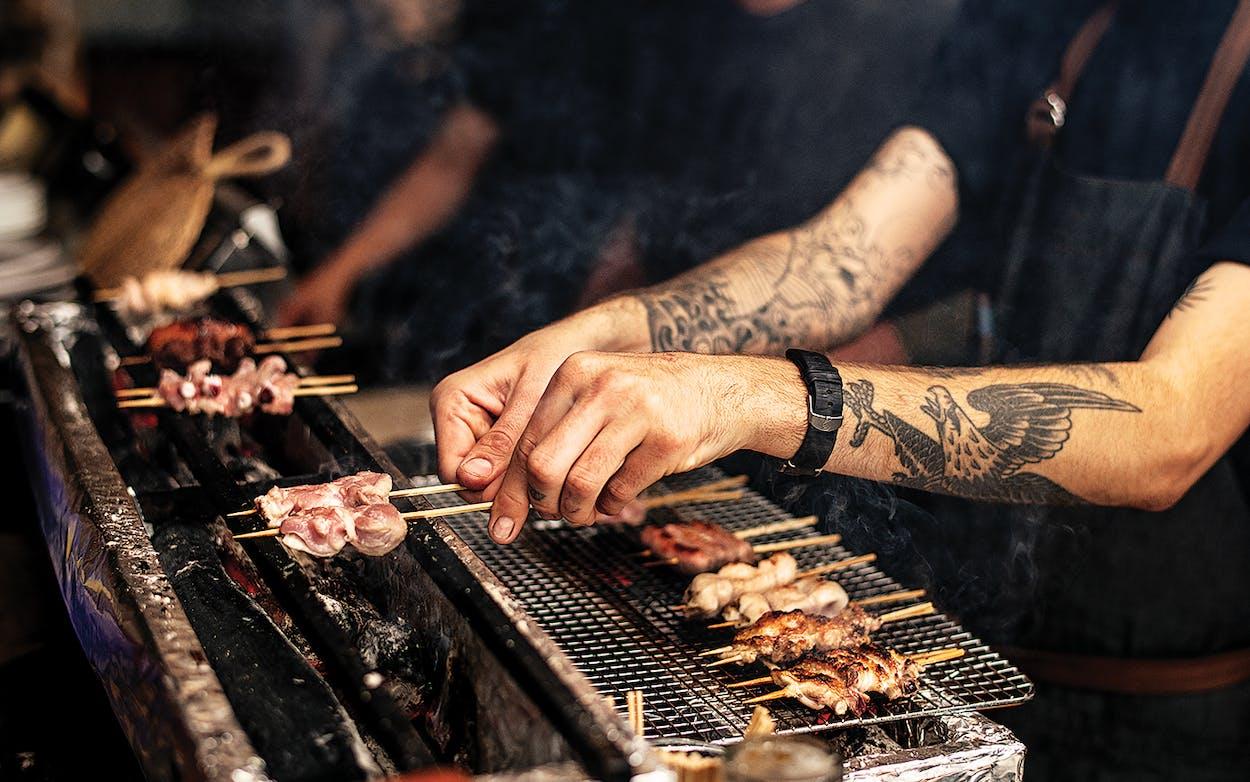 Salaryman servers cooking skewers of meat over coals