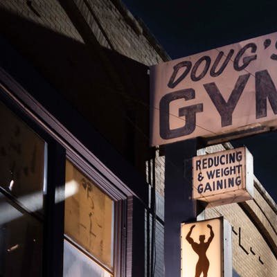 "Doug's Gym was recognized, if at all, by its vintage sign with the out-of-step promise of ""reducing & weight gaining."" It was this sign, in fact, that originally caught Diamond's eye. But when he first walked up the gym's sagging steps, the last thing on his mind was building muscle and losing weight. The truth is, Diamond was feeling a little lost. He'd recently retired from a career as a doctor specializing in interventional radiology and was, in his words, ""still coming to grips"" with thirty years of seeing people in terrible and often incurable situations. The gym's peeling paint and dark corners spoke to him—about years passing by, about mortality, and our ability to change. And so three times a week for six months he photographed a gym tinged with cigar smoke and sheltered from time."
