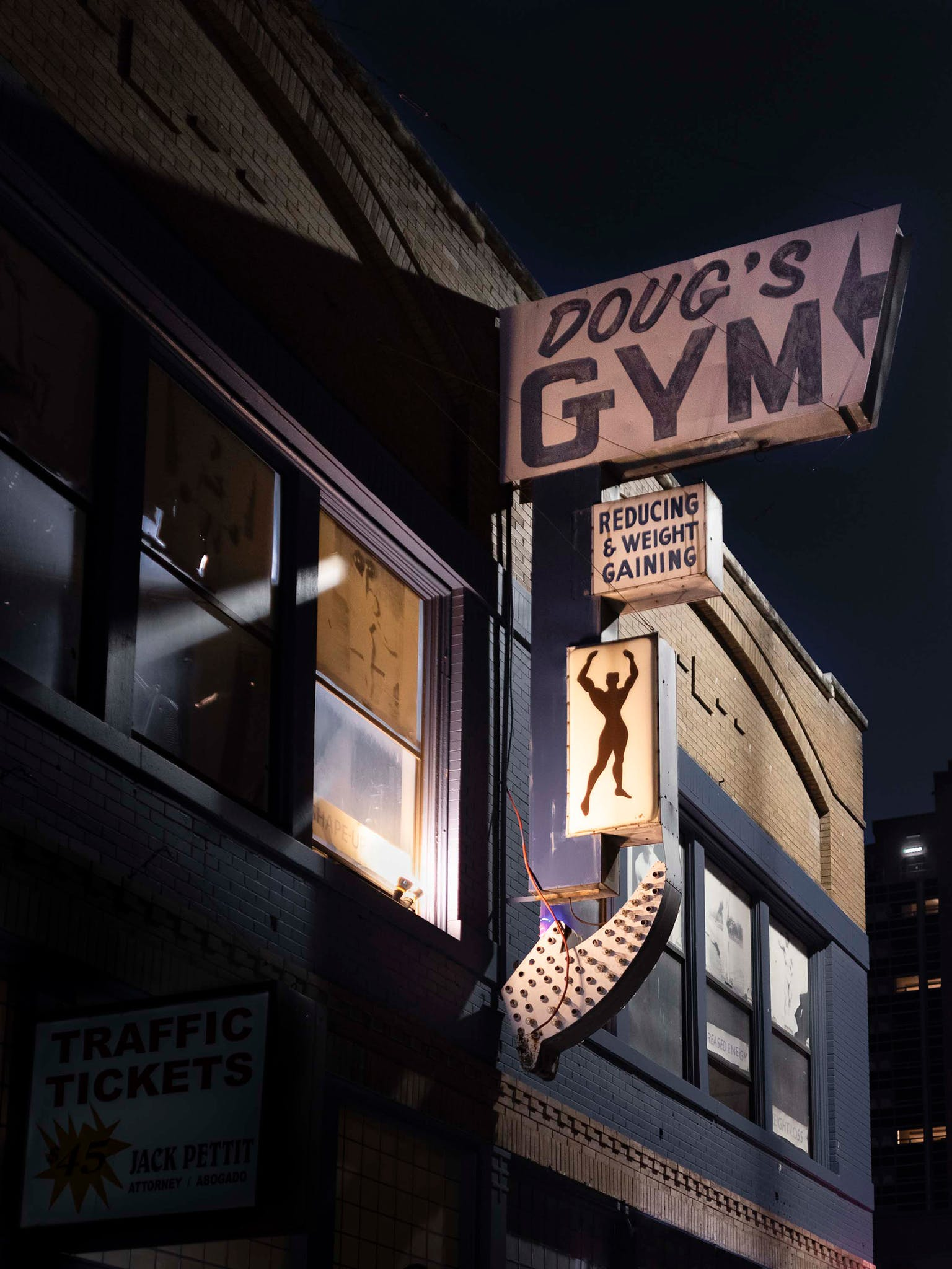 """Doug's Gym was recognized, if at all, by its vintage sign with the out-of-step promise of """"reducing & weight gaining."""" It was this sign, in fact, that originally caught Diamond's eye. But when he first walked up the gym's sagging steps, the last thing on his mind was building muscle and losing weight. The truth is, Diamond was feeling a little lost. He'd recently retired from a career as a doctor specializing in interventional radiology and was, in his words, """"still coming to grips"""" with thirty years of seeing people in terrible and often incurable situations. The gym's peeling paint and dark corners spoke to him—about years passing by, about mortality, and our ability to change. And so three times a week for six months he photographed a gym tinged with cigar smoke and sheltered from time."""