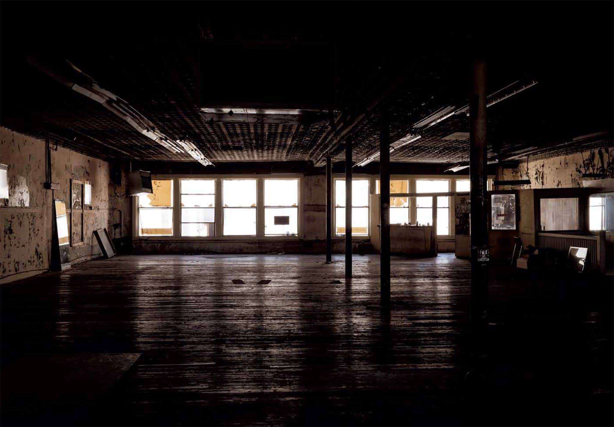 Diamond's final photo of the gym, taken on April 16, 2018, reveals the first time the space on Commerce Street had been empty since September 1962. A few of the regulars, including one old-timer who'd been working out there from the beginning, showed up to say goodbye as the last of the equipment was being dismantled. They came to show their appreciation for Eidd and for a place aggressively unconcerned with staying up to date, a place that helped people better themselves even as it continued to deteriorate. Eidd, now 89, had the equipment moved to the backyard of the home he shares with one of his sons, an hour outside of Forth Worth. In the warmer weather, some of Doug's regulars stop by, work out, catch up. Downtown Dallas continues to change but the second-floor space that once held Doug's Gym sits empty. The sign still hangs where it always has, over the street, seemingly weightless.