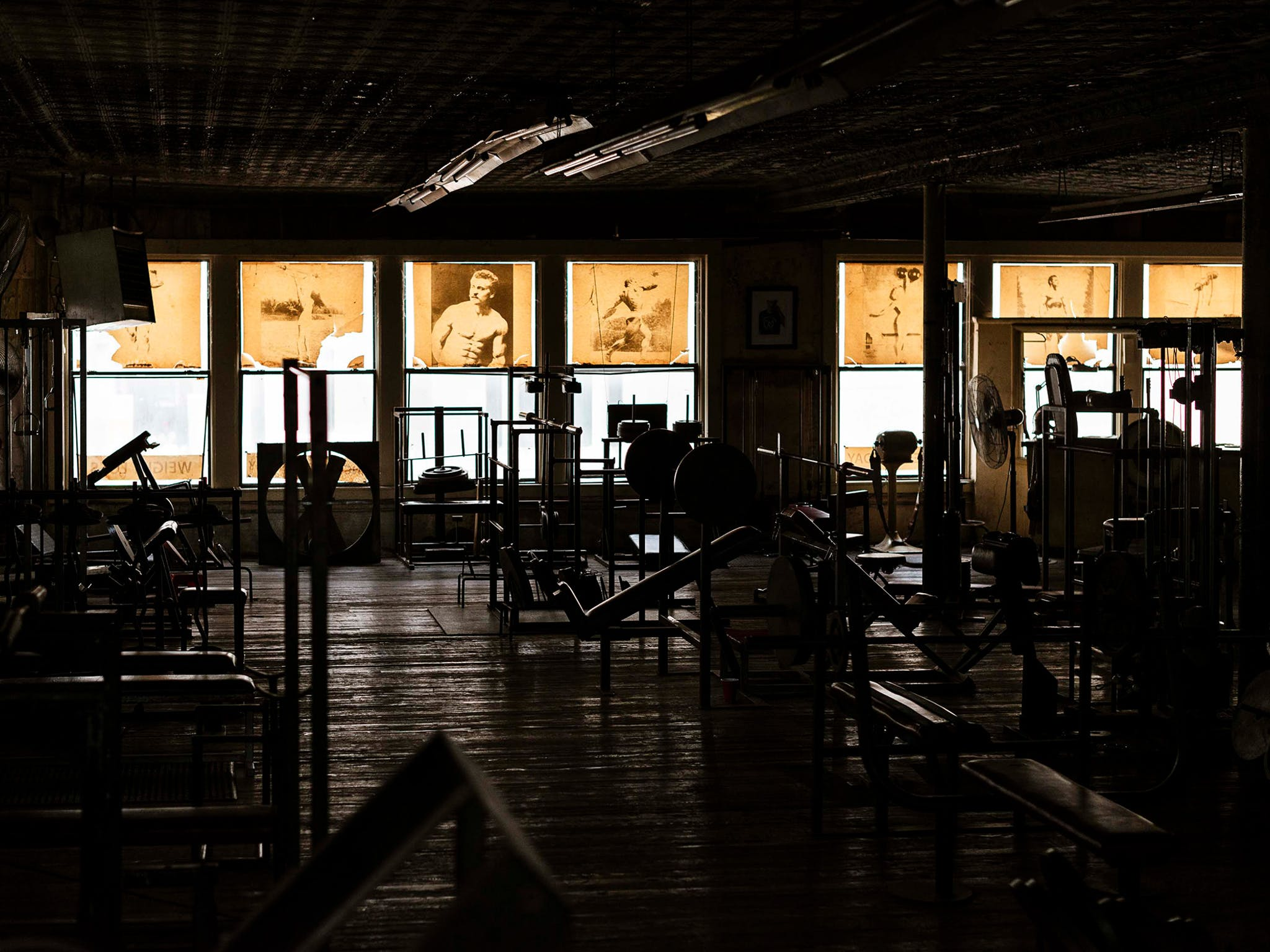 """Even during peak times, the gym rarely had more than 15 or 20 people in it, but when it was empty, it took on an entirely different mood. With the fluorescents off and the sun backlighting the yellowed posters that served as window treatments, you can make out the rough flooring (""""you wouldn't walk on that with bare feet,"""" says Diamond), the almost architectural silhouettes of the equipment, and two fans. Barely visible in the far right window: a vintage vibrating belt once considered a state-of-the-art fat-reducing device."""