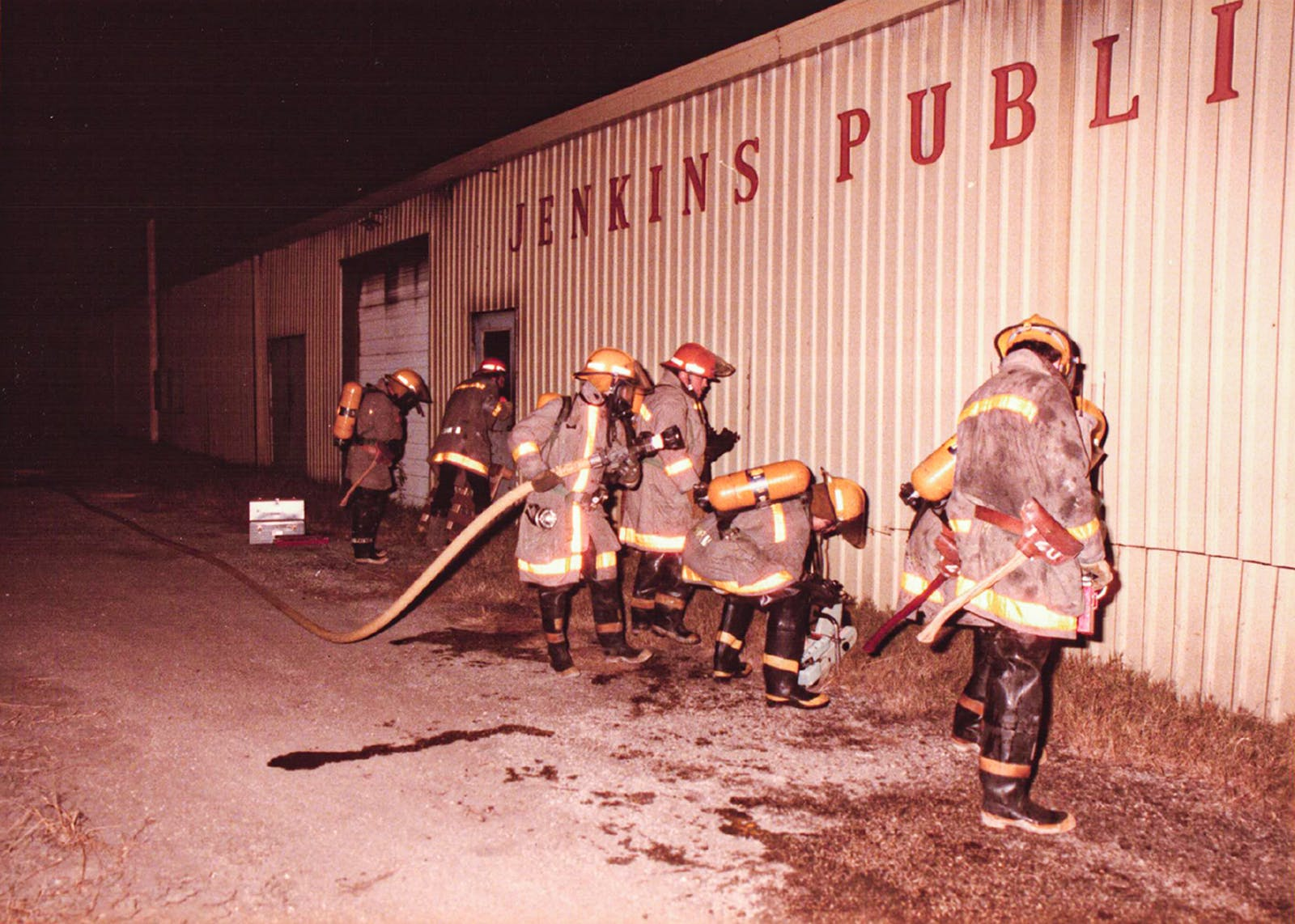 Austin Firefighters enter Jenkins Publishing Company during the 1987 fire.