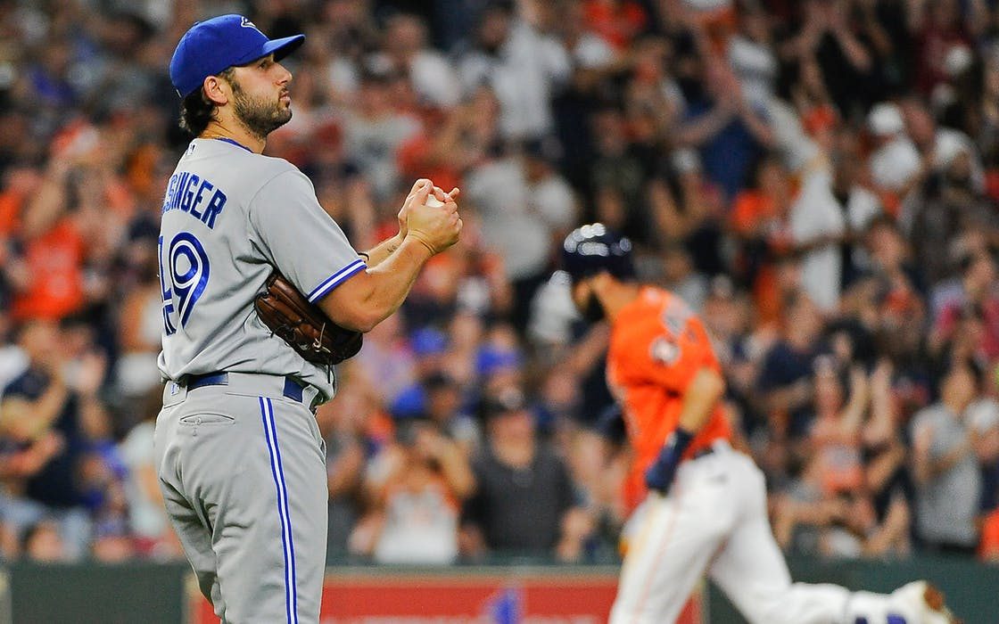 Toronto Blue Jays relief pitcher Mike Bolsinger, left, walks off the mound as Houston Astros' Marwin Gonzalez, right, rounds the bases after hitting a three-run home run during the fourth inning of a baseball game, Friday, Aug. 4, 2017, in Houston.
