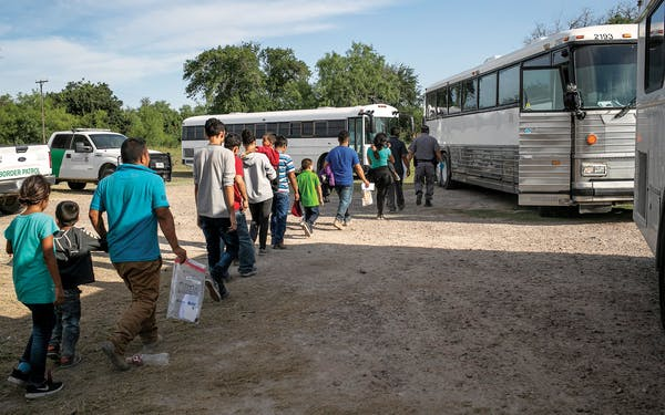 Immigrants walk to U.S. Homeland Security busses to be transferred to a U.S. Border Patrol facility in McAllen after crossing from Mexico on July 2, 2019.