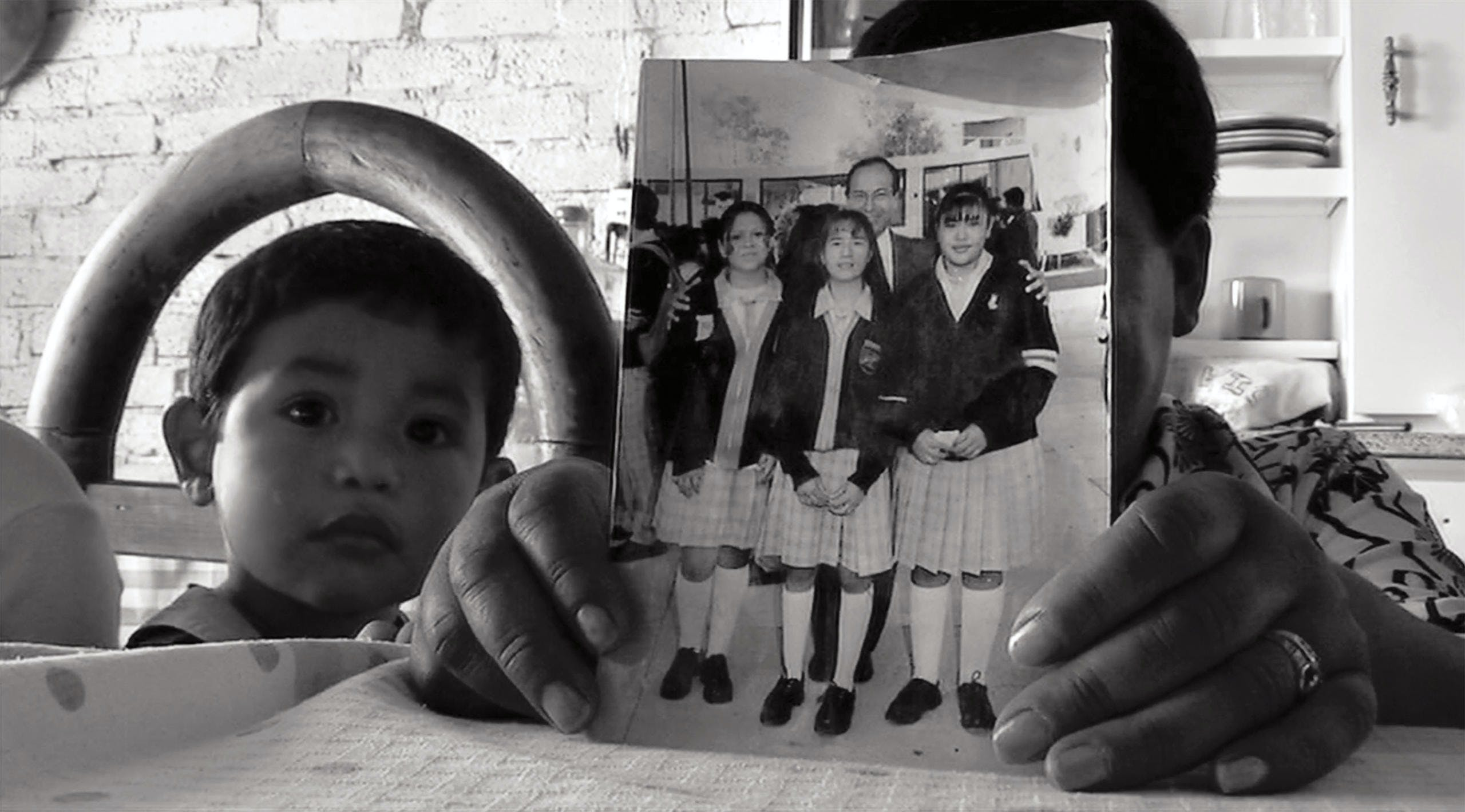In a scene from Mi Vida Dentro, Jimenez's mother holds a photo of Rosa, on the far right, that she used to show to Jimenez's kids so they'd remember their mother's face. Jimenez's son, Emmanuel, looks on at left.