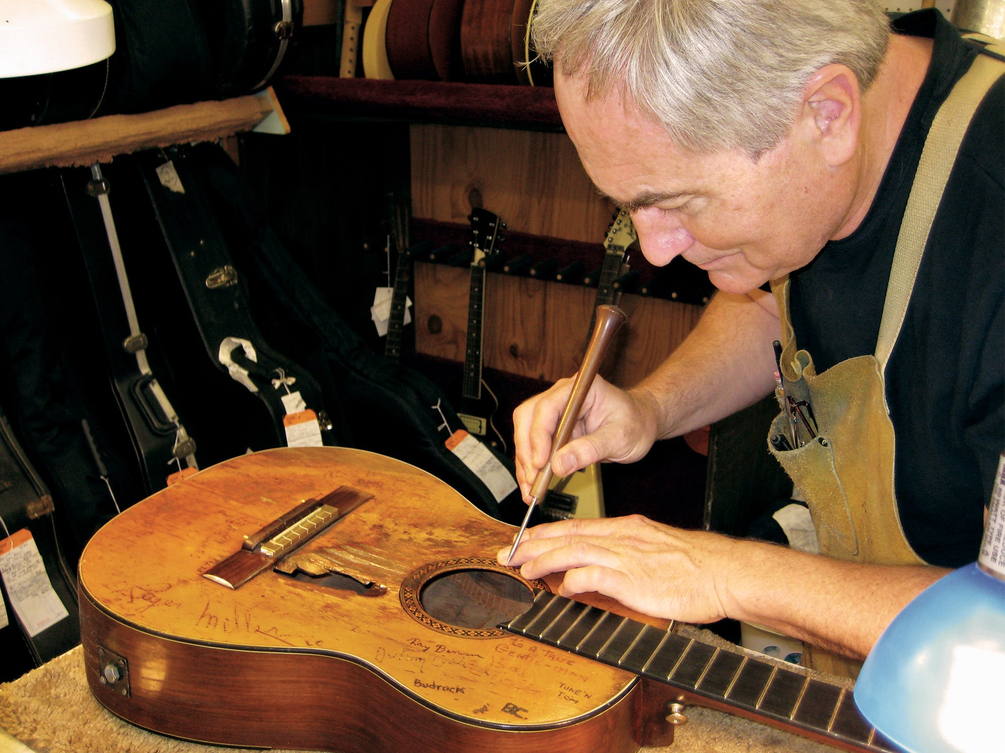 Mark Erlewine at work in his shop, cleaning the soundboard with an awl. On its tip is a piece of a diaper dipped in naphtha solvent.