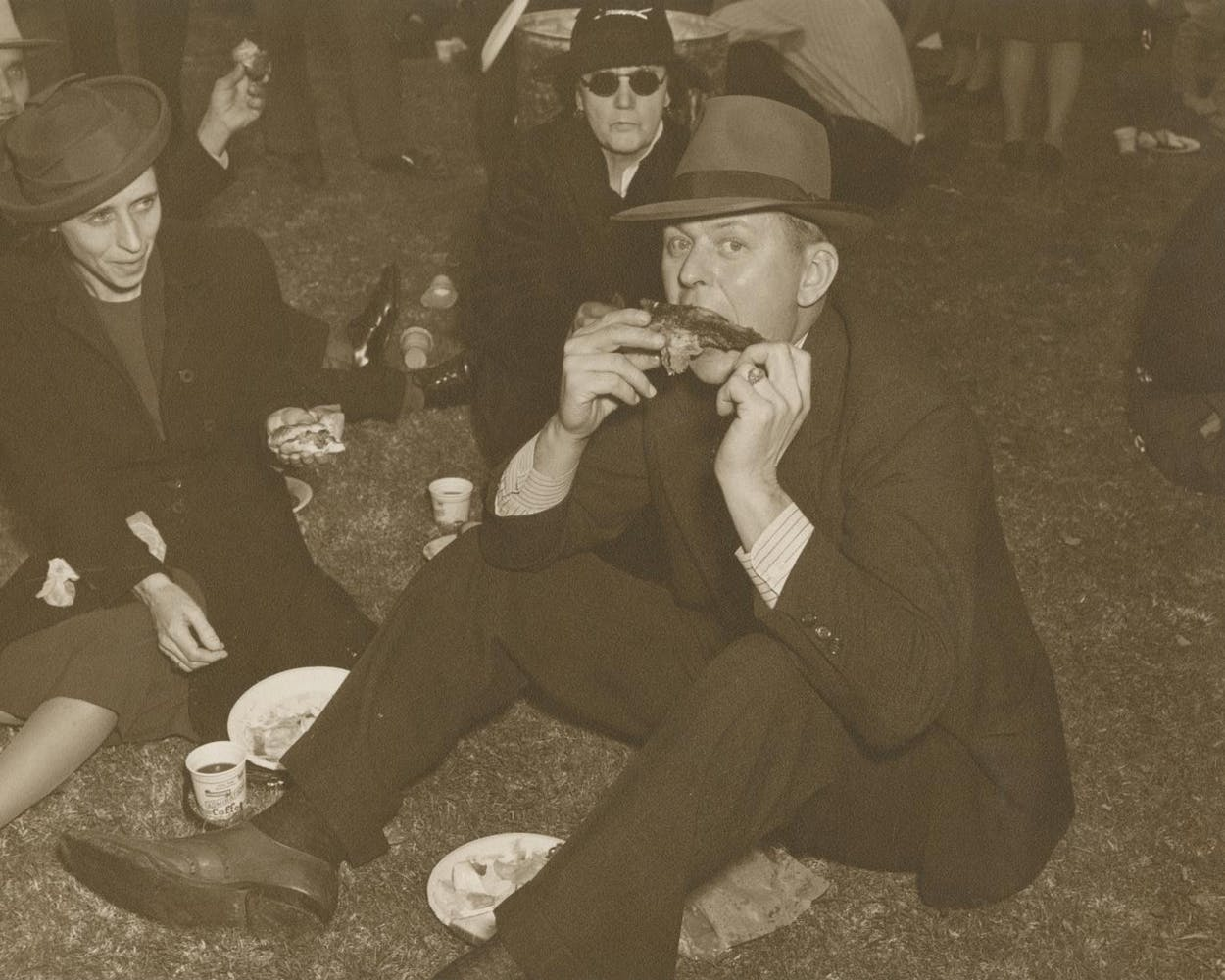 A man sitting on the ground, eating barbecue ribs, in the early 1940s.