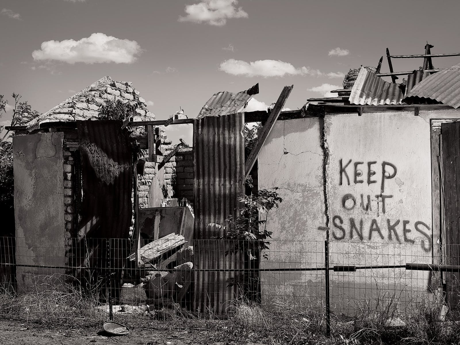 """KEEP OUT SNAKES,"" written in spray paint on an adobe ruin in Marfa."
