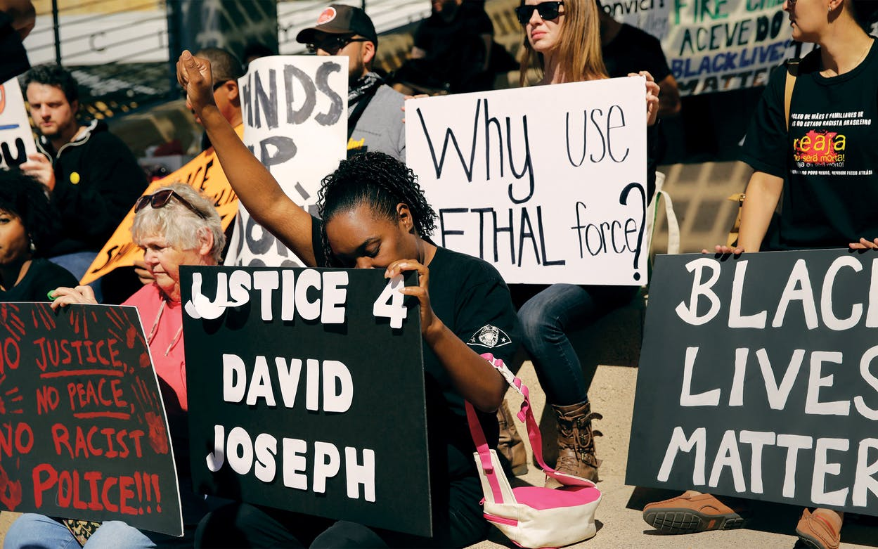 Juanita Spears, center, raises her hand during a rally at Austin City Hall in response to the recent fatal police shooting of David Joseph, 17, in Austin, on February 11, 2016. The shooting of Joseph, who was naked and unarmed, has provoked outcry among social justice activist groups.