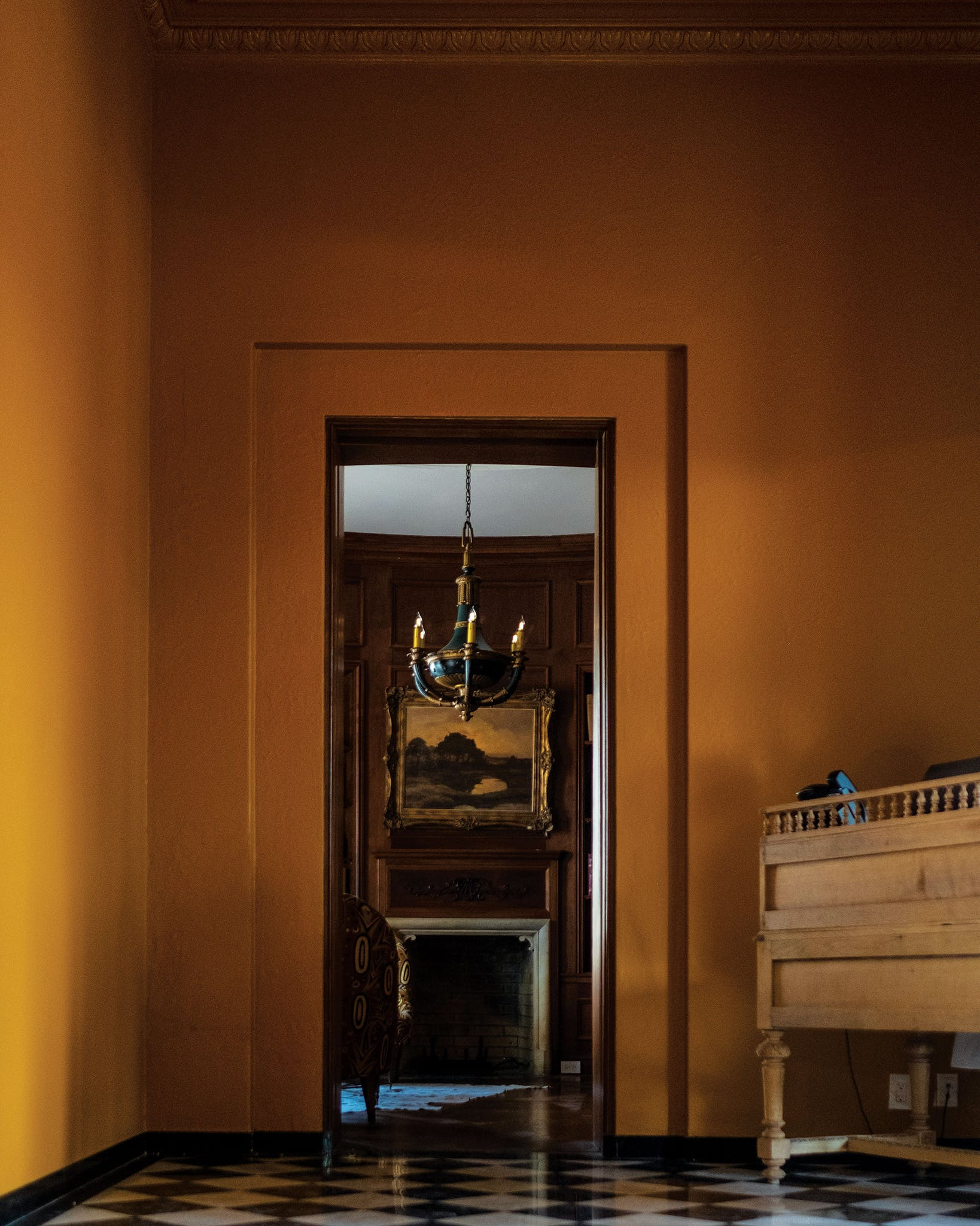 """Here, """"Perry Gold"""" again—on the walls of the mansion's entryway. If you walk into the space too quickly, you might miss the intimate, rotunda-like library, tucked away to your left."""